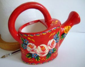 Miniature red decorative watering can