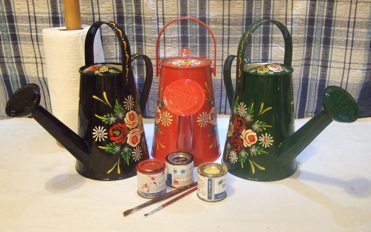 Watering cans in red, green and black